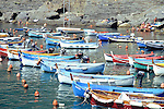 Rows of small and colorful boats line the harbor of Vernazza, in the Cinque Terre during summer in Italy.