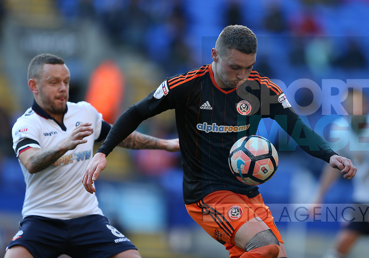 Caolan Lavery of Sheffield Utd holds off Jay Spearing of Bolton during the FA Cup Second round match at the Macron Stadium, Bolton. Picture date: December 4th, 2016. Pic Simon Bellis/Sportimage