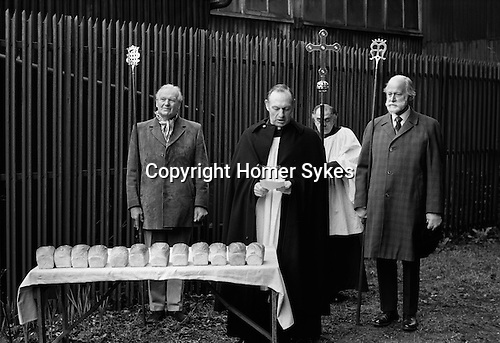 Carlow's Charity Woodbridge Suffolk.1975<br /> The Revd Canon Rowlands, accompanied by Churchwardens, Mr George Thacker (L)and Dr Hugh Porter (R),the Server is Mr Alec Grayston. Loafs of bread are distributed to those pensioners who qualify from a table set up in a back yard of the Bull Hotel. This is the site of Carlow's Tomb. <br /> <br /> George Carlow, who died in 1738, was a member of a religious sect called 'Separate Congregation', one of whose beliefs was that Saturday should be kept as the Sabbath. Before he died, Carlow had a vault built in the garden of his house, on which was inscribed :<br /> <br /> Weep for me dear friend no more for I am gone a little before.But by a lite of pity prepare yourself to follow me. Good friends for Jesus sake forbear To move the dust entombed here.<br /> Blessed be he that spares these stones. Cursed be he that moves my bones. Twenty shillings worth of bread to be given on this stone to the poor of the town on the second of February forever.