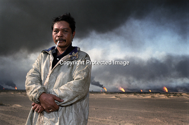 An unidentified fire fighter from the Philippines stands in the desert with oil wells burning in the background on August 7, 1991, at Greater Burhan oilfield in Kuwait. When the Gulf War ended in February 1991,the Iraqi forces retreated and hundreds of wells were blown up. Expert teams mainly from USA and Canada arrived and the last fires were put out in October 1991. (Photo by: Per-Anders Pettersson)
