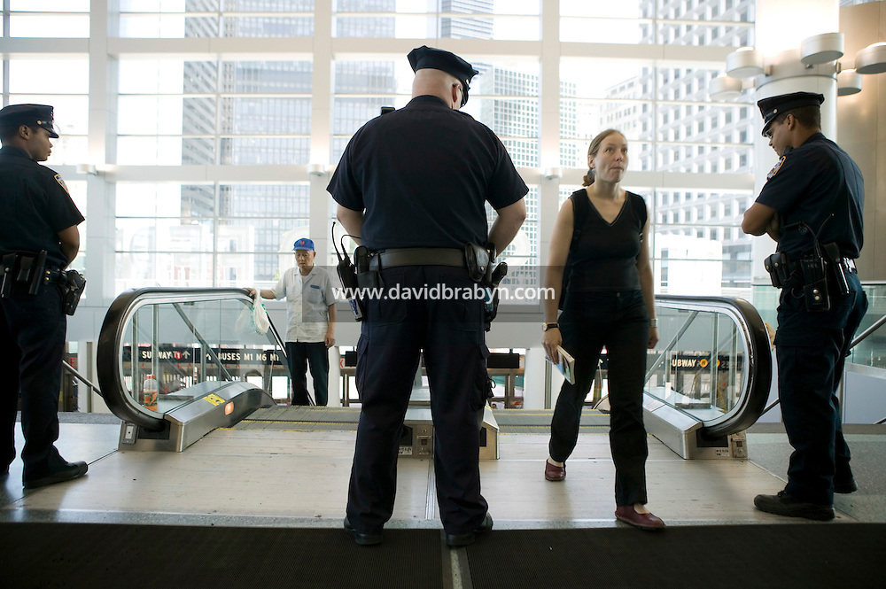 22 July 2005 - New York City, USA - Police officers (LtoR) Wooley, Clarke and Perez check passengers entering the Staten Island Ferry Terminal in Manhattan, New York City, USA, 22 July 2005. The NYPD decided to subject riders to random bag inspections following the second attack on London's transit system in two weeks. Photo Credit: David Brabyn.