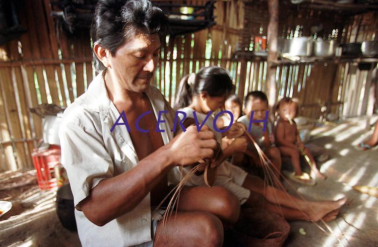 Índio Werekena Bartolo Cândido, morador da comunidade de Anamoim no alto rio Xié,começa com sua família o trabalho de beneficiamento da piaçaba (Leopoldínia píassaba Wall), para trnsformá-la em artesanato . A fibra  um dos principais produtos geradores de renda na região é  coletada de forma rudimentar. Até hoje é utilizada na fabricação de cordas para embarcações, chapéus, artesanato e principalmente vassouras, que são vendidas em várias regiões do país.<br />Alto rio Xié, fronteira do Brasil com a Venezuela a cerca de 1.000Km oeste de Manaus.<br />06/06/2002.<br />Foto: Paulo Santos/Interfoto Expedição Werekena do Xié<br /> <br /> Os índios Baré e Werekena (ou Warekena) vivem principalmente ao longo do Rio Xié e alto curso do Rio Negro, para onde grande parte deles migrou compulsoriamente em razão do contato com os não-índios, cuja história foi marcada pela violência e a exploração do trabalho extrativista. Oriundos da família lingüística aruak, hoje falam uma língua franca, o nheengatu, difundida pelos carmelitas no período colonial. Integram a área cultural conhecida como Noroeste Amazônico. (ISA)