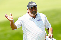 Angel Cabrera waves to the crowd following his putt on the 18th green during the 2016 U.S. Open in Oakmont, Pennsylvania on June 17, 2016. (Photo by Jared Wickerham / DKPS)