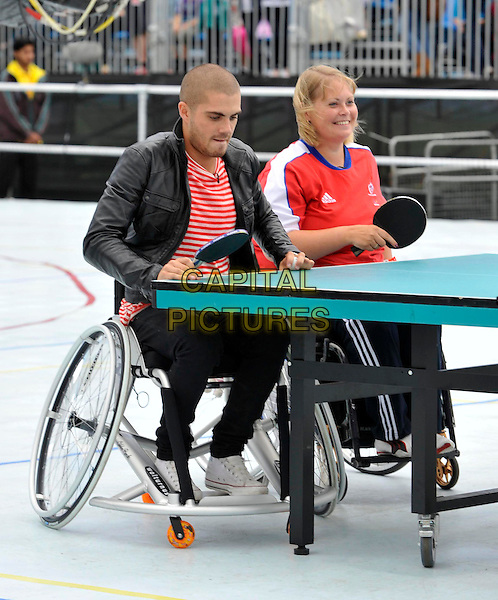 The Wanted - Max George .London - Members of boyband 'The Wanted' play 'wheelchair table tennis' as part of the Sainsburys Super Saturday. The event raises funds for the Paralympic Legacy Fund and celebrates one year to go until the Paralympic Games.  London, England..September 10th 2011.band group sitting black leather jacket sitting jeans denim red stripe top table sport paddle  ping pong full length .CAP/ROS.©Steve Ross/Capital Pictures