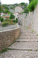 Narrow street cobble stone leading up into the village. Pocitelj historic Muslim and Christian village near Mostar. Federation Bosne i Hercegovine. Bosnia Herzegovina, Europe.