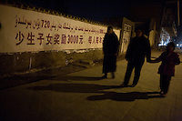 "People walk past a government billboard about money offered to Uighur families who have fewer children.  The text reads, approximately, ""Having fewer children rewards 3000yuan (about $450), that's 720yuan ($110) a person a year."""