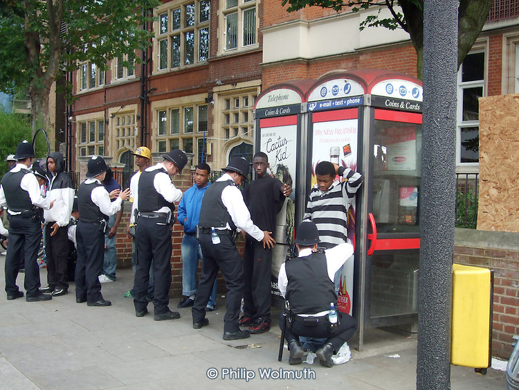 Police search a group of black boys in Notting Hill during the annual carnival.