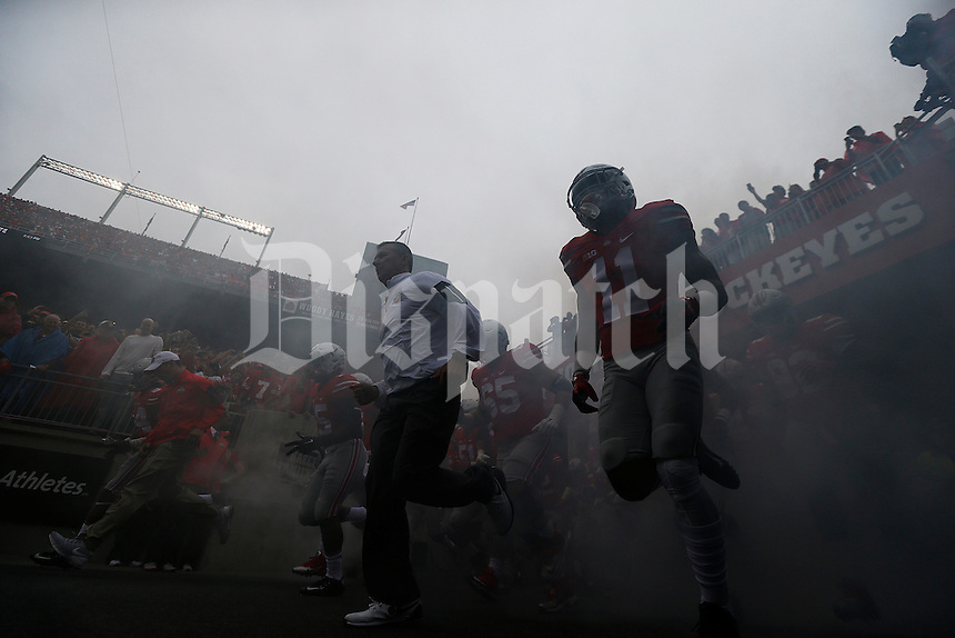 Ohio State Buckeyes head coach Urban Meyer and his team run on to the field before the college football game between the Ohio State Buckeyes and the Northern Illinois Huskies at Ohio Stadium in Columbus, Saturday afternoon, September 19, 2015. As of half time the Ohio State Buckeyes were tied with the Northern Illinois Huskies 10 - 10. (The Columbus Dispatch / Eamon Queeney)