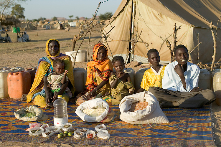 (MODEL RELEASED IMAGE). The Aboubakar family of Darfur province, Sudan, in front of their tent in the Breidjing Refugee Camp, in eastern Chad, with a week's worth of food. D'jimia Ishakh Souleymane, 40, holds her daughter Hawa, 2; the other children are (left to right) Acha, 12, Mariam, 5, Youssouf, 8, and Abdel Kerim, 16. Cooking method: wood fire. Food preservation: natural drying. Favorite food: D'jimia: soup with fresh sheep meat. The Aboubakar family is one of the thirty families featured in the book Hungry Planet: What the World Eats (p. 56).