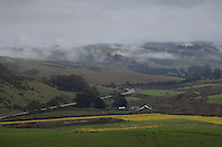 Tufts of fog float over a valley and along the Santa Cruz Mountains footills near San Gregorio on California's Central Coast.