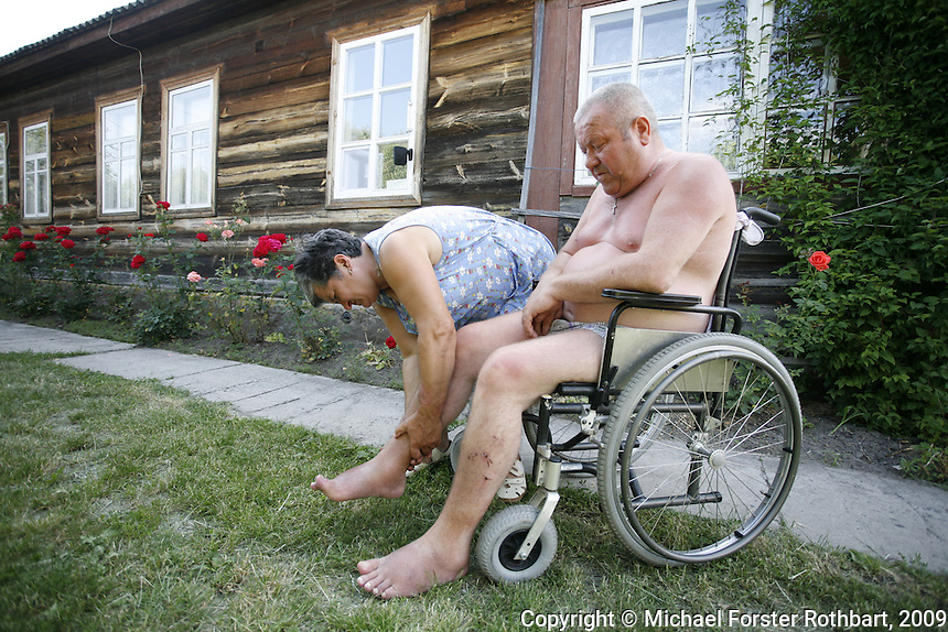 Leonid Budkovskiy, a mail carrier from Ivankiv, was reassigned to deliver military mail after the accident. He entered the exclusion zone daily. Although his drivers quit over fears of radiation, Leonid continued for almost five years out of a patriotic sense of duty. In 1990, his knees started to swell. His legs slowly stopped working. By 1996, he was confined to a wheelchair. &ldquo;In Chernobyl, no one knew how serious it was. We wore no special clothes,&rdquo; Leonid says. &ldquo;I am 55 years old, and no one needs me. I can still hold a spoon, but I need help to go the bathroom and I have to wear diapers.&rdquo; He spends summer days sitting on his back stoop, overlooking his wife&rsquo;s vegetable garden.<br /> ------------------- <br /> This photograph is part the book of Would You Stay?, by Michael Forster Rothbart, published by TED Books in 2013. The photos come from Forster Rothbart&rsquo;s two long-term documentary photography projects, After Chernobyl and After Fukushima.<br /> &copy; Michael Forster Rothbart 2007-2013.<br /> www.afterchernobyl.com<br /> www.mfrphoto.com &bull; 607-267-4893 &bull; 607-436-2856 <br /> 34 Spruce St, Oneonta, NY 13820<br /> 86 Three Mile Pond Rd, Vassalboro, ME 04989<br /> info@mfrphoto.com<br /> Photo by: Michael Forster Rothbart<br /> Date:  7/2009    File#:  Canon 5D digital camera frame 79493