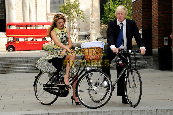KELLY BROOK & BORIS JOHNSON.Photocall to launch the Mayor of London's 'Skyride' a free cycling event with traffic free roads, London, England. .September 8th, 2009.full length black suit sleeveless lace floral print dress bike bicycle basket looking down wind windy blowing slip.CAP/CAS.©Bob Cass/Capital Pictures.