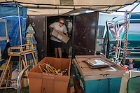 NWA Democrat-Gazette/ANTHONY REYES • @NWATONYR<br /> Kayla Gilmore, of Springfield, Mo., sets up a booth Thursday, Sept. 17, 2015 at the Foot Hills of the Ozarks Swap Meet at Parsons Stadium in Springdale. Gilmore and her father travel around to different meets selling a variety of goods, including Ferrari parts, neon signs, and gas station memoriabilia, have their own booth at the swap meet but took a minute to look at a neighboring booth. The meet continues today and Saturday.