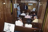 "Kansas City, Missouri, September 9, 1978. Paul Phillips is a driver of the Truck ""Transport for Christ"" and in the mean time he is a Chaplain. People are coming in the trailer for Religious Service."