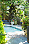Lush container plantings surround the spa and seating area of a back deck.