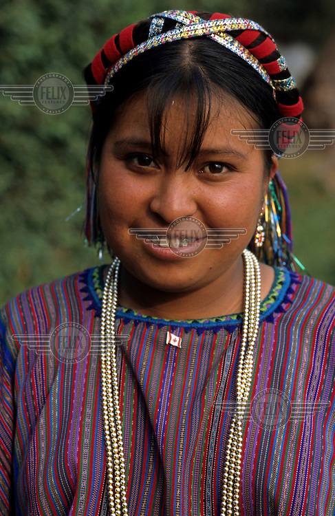 A portrait of a young Maya woman in San Antonio Palopo. She is wearing a huipil (a traditional woven and embroidered cotton blouse) and a headdress typical of her village.