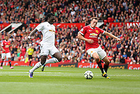 Pictured L-R: Bafetimbi Gomis of Swansea against Phil Jones of Manchester United. Saturday 16 August 2014<br />