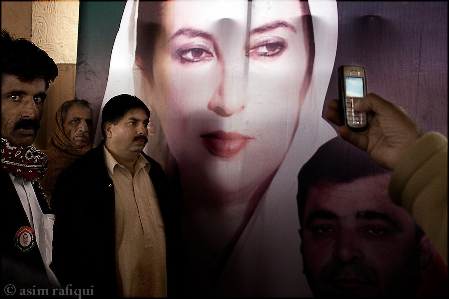 Pakistan People's Party (PPP) supporters have their pictures taken in front of a poster of Benazir Bhutto on the occasion of the 40th day of mourning after her assasination.