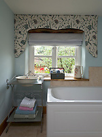 An old-fashioned wrought-iron washstand and basin in a  bathroom with a fresh blue-and-white palette