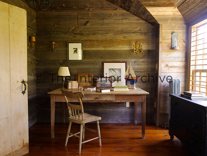 The walls and floor of the study are made of barn wood and the room, like the rest of the house, is simply furnished