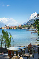 Italy, Veneto, Lake Garda, Malcesine: café at lakeside promenade Via Lungolago with view towards old town and castle | Italien, Venetien, Gardasee, Malcesine: Café an der Via Lungolago mit Blick zur Altstadt und Scaligerburg