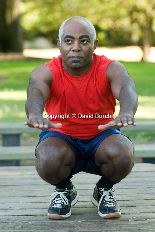 Mature man exercising,deep knee bends, front view