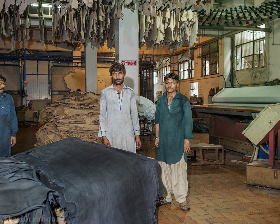 Workers at a drying station. A large heater/ dryer is used to stretch and dry recently washed and dyed sheets of leather. These sheets are pinned onto the nets as they move through the 'toaster' like drying machines. Skins are then air dried for 2-3 days depending of the temperature and humidity inside the factory and can take up to 1 week in particularily cold or wet weather.