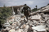 In this Sunday, Sep. 22, 2013 photo, an opposition fighter walks among the rubbish of a house demolished by a warplane bomb in Kafr Zita, a village turned into a battlefield where clashes between troops loyal to president Bashar Al-Assad and opposition fighters have broke out for the control of the region in the Idlib province countryside, Syria. (Photo/AP).