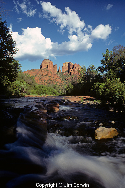 Cathedral Rocks from Oak Creek Canyon Red Rock Crossing with storm clouds over rock formations and small waterfall in foreground Sedona Arizona State USA.