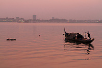 A fisherman rawing on the Mekong river along Phnom Penh during sunset, Cambodia - 2011