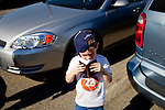 Isaac Williams, 5, looks in a Bible in the National Hills Baptist Church's lot, while his older brother prays for a person who parked in the lot. The church, which is surrounded by lots charging $20, is just one block from Augusta National Golf Course in Augusta, Georgia April 6, 2010. The church members offered free coffee and parking, along with prayers that car owners requested and filled out on cards and left on their windshields in the lot.