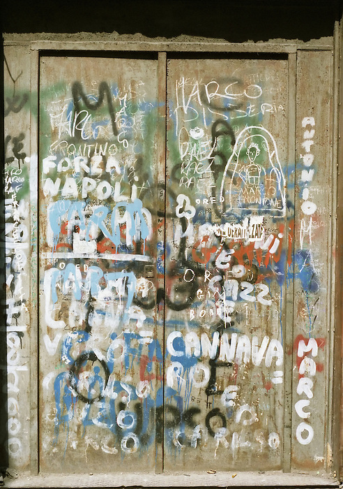 A metal door covered in graffiti on a street in Naples. Italy 20003.