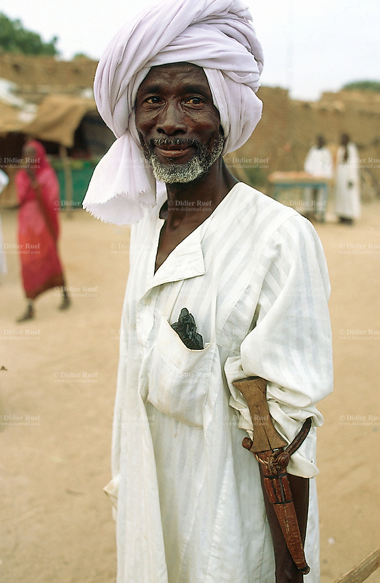 Sudan. West Darfur. Kerenek. A smiling old man, dressed with white clothes and a turban on the head, stands on the dirt road. He has a knife fixed on his arm. © 2004 Didier Ruef