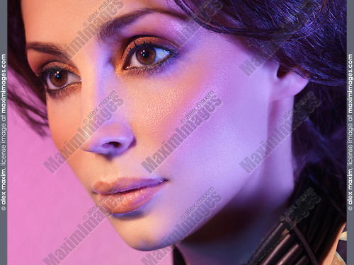 Closeup portrait of a beautiful woman face with artistic makeup and colored purple light