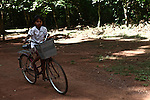 A girl rides her bicycle at Angkor Wat, Cambodia. June 7, 2013.