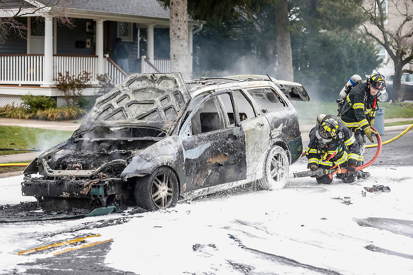 MANASQUAN, NJ — April 1, 2016 — Manasquan firefighters use foam to battle a stubborn car fire on Broad Street at about 9:40am Friday morning. The driver of the vehicle was not injured.  photo by Andrew Mills