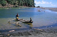 Melanesian man and his children in a traditional dugout canoe in the estuary at Sulphur Bay, Tanna, Vanuatu.