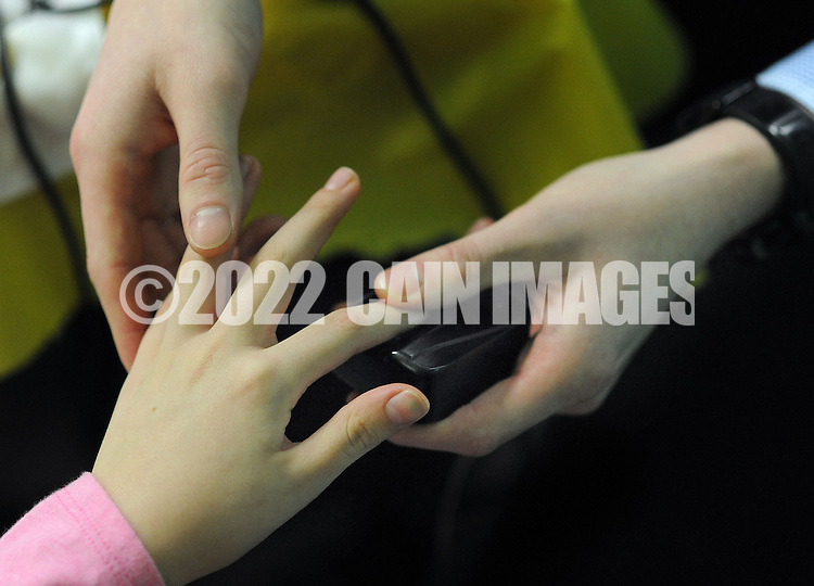 WARRINGTON, PA. - JANUARY 24: Thomas J. Arters of New York Life takes fingerprints from Julia Trumbo, 10, of Warrington, Pennsylvania during an open house at The Little Gym January 24, 2015 in Warrington, Pennsylvania. New York Life created Child Fingerprint ID cards for all in attendance. The Child ID's include a child's photo, digitally-scanned fingerprints, and emergency contact information. (Photo by William Thomas Cain/Cain Images)
