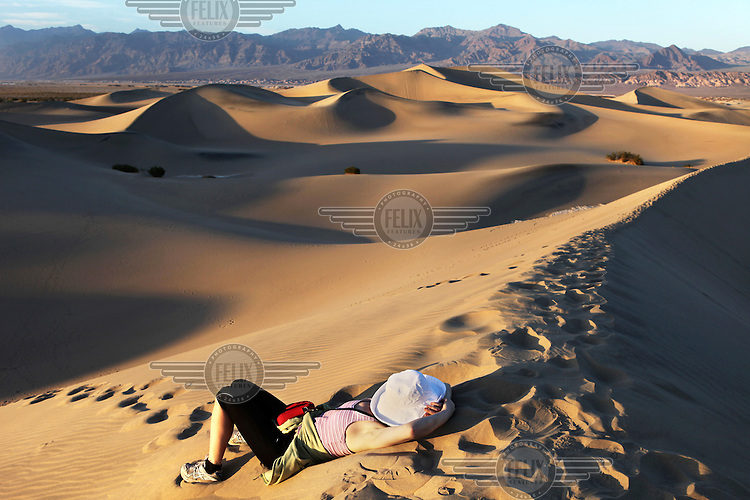 A woman rests in the Death Valley National Park, California. Death Valley is situated in the Mojave Desert. It features the lowest, driest, and hottest locations in North America. It holds the record for the highest reliably reported temperature in the Western hemisphere. ..