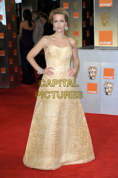 Gillian Anderson .The Orange British Academy Film Awards ( BAFTA ), Royal Opera House, Bow St., London, England..February 12th, 2012.baftas full length dress long maxi hands on hips strapless gold yellow   .CAP/PL.©Phil Loftus/Capital Pictures.