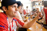 Paraguay fan Pier Pappalgrodo watches his team play England at a bar in New York City on June 10, 2006.  <br /> <br /> The World Cup, held every four years in different locales, is the world's pre-eminent sports tournament in the world's most popular sport, soccer (or football, as most of the world calls it).  Qualification for the World Cup is open to any country with a national team accredited by FIFA, world soccer's governing body. The first World Cup, organized by FIFA in response to the popularity of the first Olympic Games' soccer tournaments, was held in 1930 in Uruguay and was participated in by 13 nations.    <br /> <br /> As of 2010 there are 208 such teams.  The final field of the World Cup is narrowed down to 32 national teams in the three years preceding the tournament, with each region of the world allotted a specific number of spots.  <br /> <br /> The World Cup is the most widely regularly watched event in the world, with soccer teams being a source of national pride.  In most nations, the whole country is at a standstill when their team is playing in the tournament, everyone's eyes glued to their televisions or their ears to the radio, to see if their team will prevail.  While the United States in general is a conspicuous exception to the grip of World Cup fever there is one city that is a rather large exception to that rule.  In New York City, the most diverse city in a nation of immigrants, the melting pot that is America is on full display as fans of all nations gather in all possible venues to watch their teams and celebrate where they have come from.
