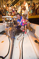 A little girl touches a Pacific blue marlin grander (1,000-lb. or more fish) as fishing boat captain Bomboy Llanes holds her on the Lana Kila, Kailua-Kona, Big Island.