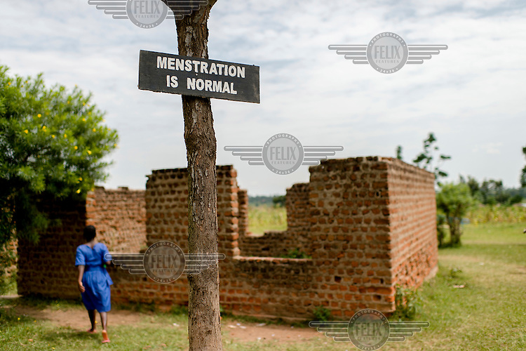 A misspelled sign nailed to a tree that reads: 'Menstruation is Normal' at Aputiri Primary School.