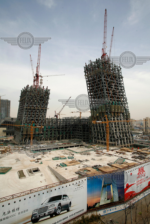 The new 550,000 square metre headquarters of China Central Television (CCTV). The building, designed by Rem Koolhaas, will be among the first of 300 new towers to be constructed in Beijing's new central business district (CBD). An artist's impression of what it will look like can be seen on a billboard at the bottom of the picture.