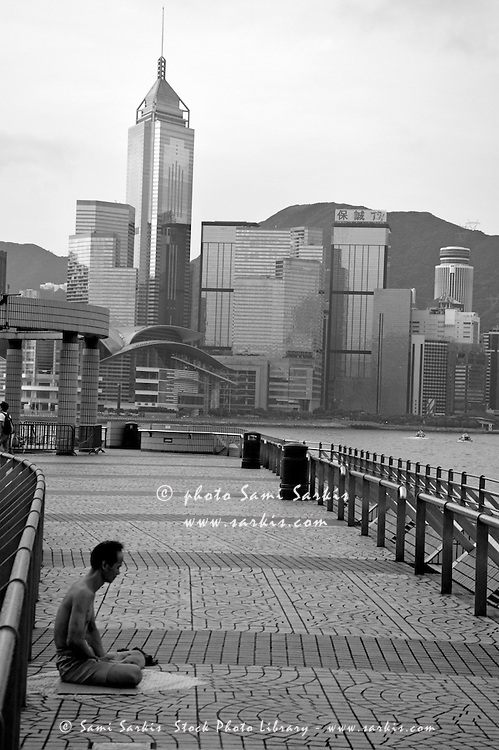 Seated man practicing yoga with view of skyline in the background, Kowloon, Hong Kong, China.