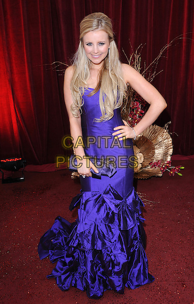 CARLY STENSON.Arrivals at the British Soap Awards 2010, London Television Centre, London, England..May 8th, 2010.full length purple long maxi dress hand on hip ruffles tiered ruffle clutch bag bow silk satin.CAP/BEL.©Tom Belcher/Capital Pictures.