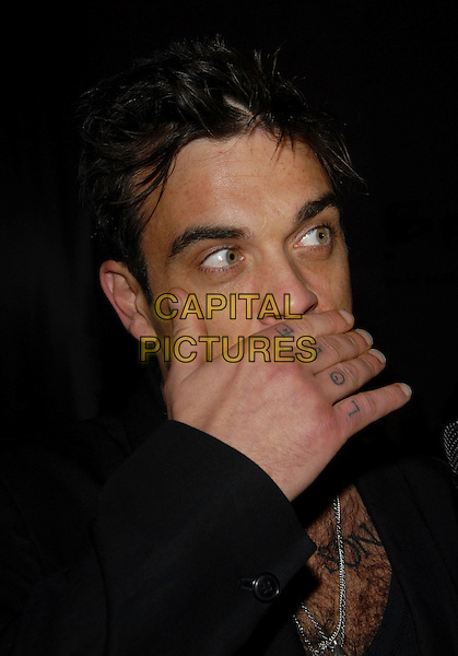 ROBBIE WILLIAMS.attends The 2 B Free Fashion Show held at Boulevard3  in Hollywood, LA, California, USA, March 19 2007..portrait headshot hand over mouth face tattoos love hand knuckles.CAP/DVS.©Debbie VanStory/Capital Pictures