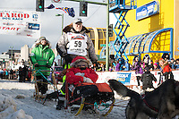 Jeff King and team leave the ceremonial start line with an Iditarider at 4th Avenue and D street in downtown Anchorage, Alaska during the 2015 Iditarod race. Photo by Jim Kohl/IditarodPhotos.com