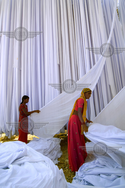 Lengths of dyed sari dry on bamboo drying racks. This centre is the most prolific in India for the dying and printing of saris reaching markets all over the country.