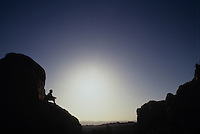 Silhouette of boy sitting on rock-Arches National Park, Utah